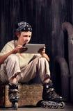 Adolescent s'asseyant avec le PC de comprimé Image libre de droits