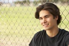 Adolescent s'asseyant dans la cour de jeu Photos stock
