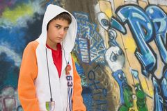 Adolescent s'asseyant près d'un mur de graffiti Photo stock