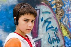 Adolescent s'asseyant près d'un mur de graffiti Photographie stock libre de droits