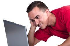 Adolescent s'asseyant sur l'étage avec l'ordinateur Photographie stock libre de droits