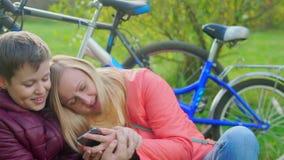 Adolescent s'asseyant sur l'herbe avec sa mère La dépendance à l'égard des smartphones clips vidéos