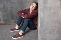 Adolescent s'asseyant sur le plancher et regardant loin photographie stock