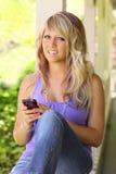 Adolescent s'asseyant sur le porche avec le téléphone portable photos libres de droits