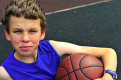 Adolescent s'asseyant sur le terrain de basket Photographie stock libre de droits