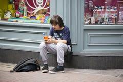 Adolescent s'asseyant sur le trottoir près du magasin, amis de attente Photographie stock
