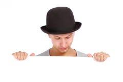 Adolescent se cachant derrière un panneau-réclame Image stock