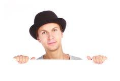 Adolescent se cachant derrière un panneau-réclame Images stock