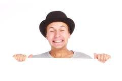 Adolescent se cachant derrière un panneau-réclame Photographie stock libre de droits