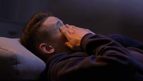 Adolescent somnolent se réveillant au sofa après gueule de bois de partie, sentiment confus banque de vidéos