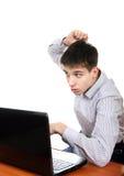 Adolescent soumis à une contrainte avec l'ordinateur portable image libre de droits