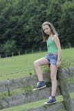 Adolescent standing on fence Royalty Free Stock Images