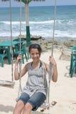 Adolescent sur l'oscillation de plage Images libres de droits