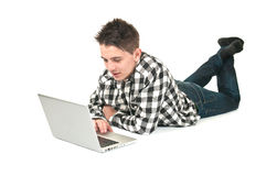 Adolescent sur un ordinateur portatif Photographie stock libre de droits