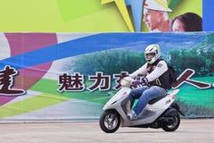 Adolescent sur un scooter de gaz avec le panneau d'affichage sur le fond, Pékin, Chine Image stock