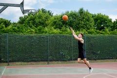 Adolescent sur un terrain de basket Image stock