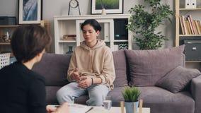 Adolescent timide parlant au psychologue féminin pendant la consultation dans la clinique banque de vidéos