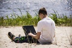 Adolescent travaillant pour un ordinateur portable sur la plage Photo stock