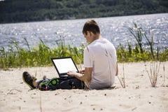 Adolescent travaillant pour un ordinateur portable sur la plage Images libres de droits