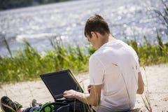 Adolescent travaillant pour un ordinateur portable sur la plage Image stock