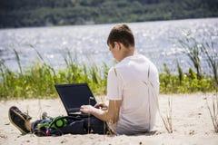 Adolescent travaillant pour un ordinateur portable sur la plage Images stock