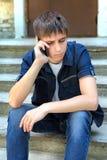 Adolescent triste avec le téléphone portable Image libre de droits