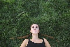 Adolescent triste recherchant sur l'herbe Photo stock