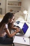 Adolescente à l'aide de l'ordinateur portable à un bureau dans sa chambre à coucher, verticale Images stock