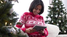 Adolescente à l'aide du comprimé numérique pendant le Noël banque de vidéos