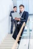 Adolescente à l'aide du portable à l'extérieur Jeune et réussi homme d'affaires se tenant dessus Image stock