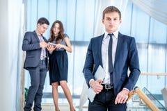 Adolescente à l'aide du portable à l'extérieur Jeune et réussi homme d'affaires se tenant dessus Images stock