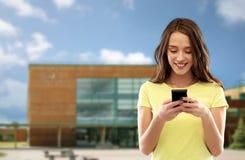 Adolescente à l'aide du smartphone au-dessus de l'école photos stock