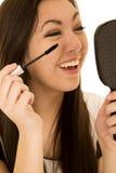 Adolescente étnico lindo aplicando su rimel que lleva a cabo una risa del espejo Imagen de archivo