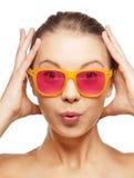 Adolescente étonnée dans des lunettes de soleil roses Photographie stock