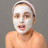 Adolescente étonnée regardant le masque protecteur d'appareil-photo Images stock