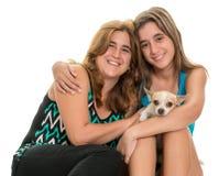 Adolescente étreignant sa mère et leur petit chien Image stock