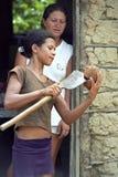 Adolescente abra un coco para su hogar simple de la niñez Imagen de archivo libre de regalías