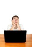 Adolescente aburrido con el ordenador portátil Imagenes de archivo