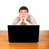 Adolescente aburrido con el ordenador portátil Imágenes de archivo libres de regalías