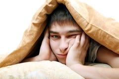Adolescente aburrido debajo de la manta Fotografía de archivo