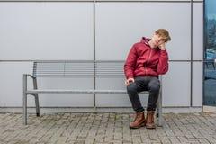 Adolescente aburrido que se sienta en el banco al aire libre en ciudad Imagen de archivo