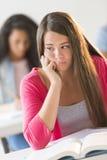 Adolescente aburrido que se sienta en sala de clase Fotografía de archivo libre de regalías