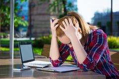 Adolescente aburrido que trabaja con el ordenador portátil en parque Imagenes de archivo
