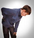 Adolescente adolescente del muchacho de los controles del osteochondrosis gris su mano detrás Imagen de archivo