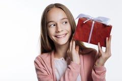 Adolescente adorable que mira la caja con el presente Foto de archivo