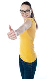 Adolescente affascinante che gesturing thumbs-up Fotografia Stock