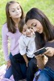 Adolescente affichant le téléphone portable aux enfants de mêmes parents photo libre de droits