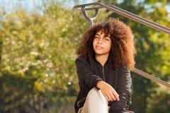Adolescente africano que se sienta en el parque en otoño Fotos de archivo libres de regalías