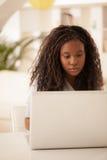 Adolescente africano que usa el ordenador portátil en casa Fotos de archivo