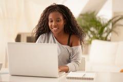 Adolescente africano sonriente que usa el ordenador portátil en casa Fotos de archivo